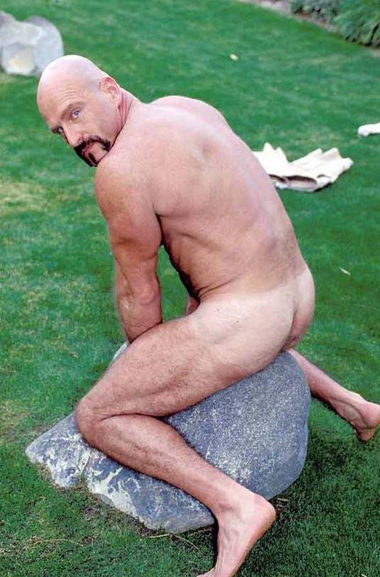 Голый гей лежит на камне